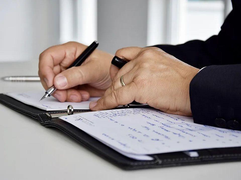 Nahaufnahme Hände beim Schreiben in ein Notizbuch